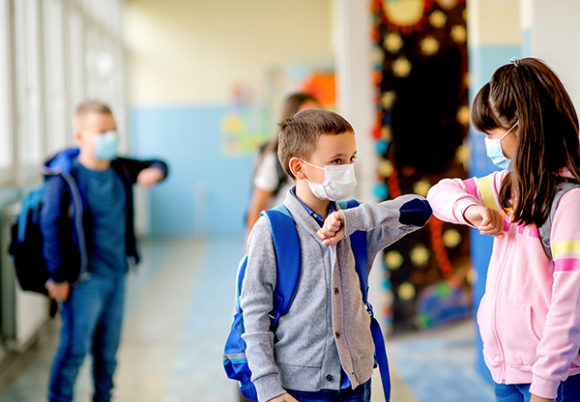 Barn med ansiktsmask hälsar på varandra med armbågen