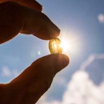 Kapsel med D-vitamin hålls mellan två fingrar framför solen