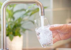 Vattenglas fylls på med vatten från kran