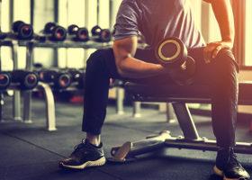 Man sitter på bänk på gymmet och lyfter hantel