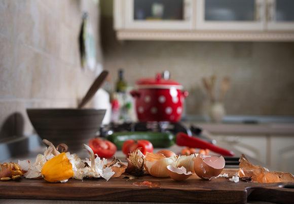 Matrester på en köksbänk med en stekpanna och en röd kastrull i bakgrunden