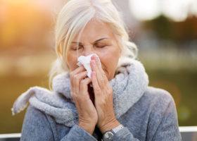 Sjuk medelålders kvinna snyter sig