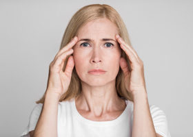 Ledsen medelålders kvinna lider av stark huvudvärk