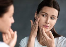 Närbild på olycklig kvinna som tittar på sina hudproblem och akne i spegeln