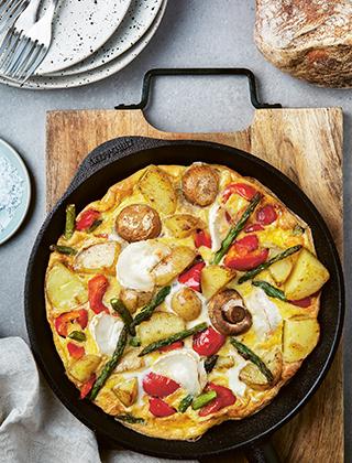 En omelett med chèvre och tomater i en stekpanna