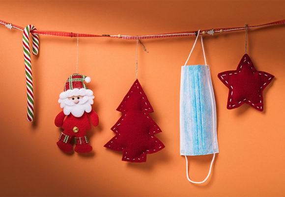 Juldekorationer, polkagrisar och tomtar och en munskydd som hänger på ett dekorativt band mot en orange vägg.