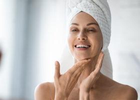 Kvinna med håret insvept i en handduk som tar hand om sin hy