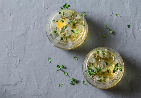 Två glas med kombucha dekorerade med timjan, mot en grå bakgrund