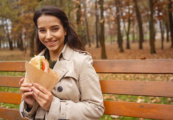En kvinna i trenchcoat äter sin lunchmacka utomhus på en parkbänk