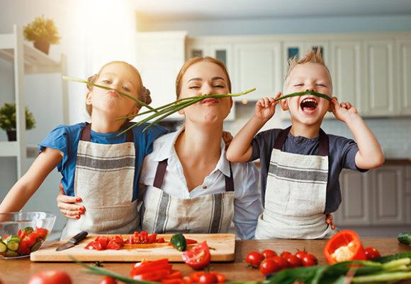 mamma med två barn förbereder sallad, skrattar och har roligt när de lagar mat