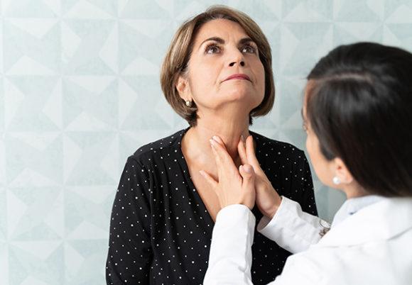 Doktor känner på patients hals