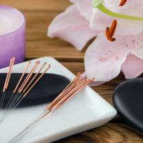 Akupunkturnålar bredvid ljus och orkidé