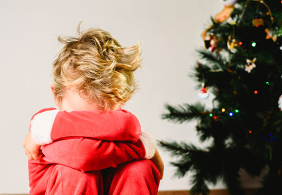 Pojke i tomtekläder sitter med ansiktet dolt i armarna framför en julgran