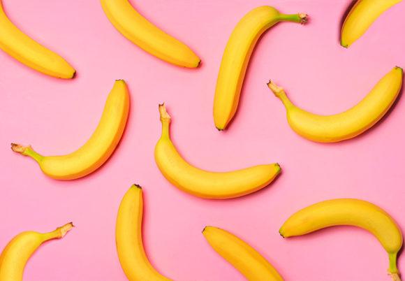 Fruktmönster av bananer över en rosa bakgrund