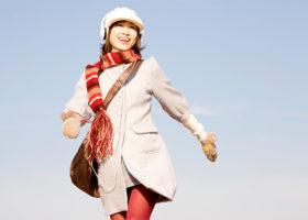Lycklig kvinna i halsduk och ljus kappa som promenerar och lyssnar på musik i hörlurar.