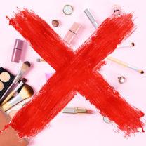 kosmetika och sminkprodukter mot rosa bakgrund med ett överstruket rött kryss