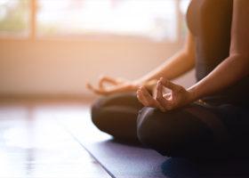 Kvinna på en yogamatta i en träningssal som mediterar