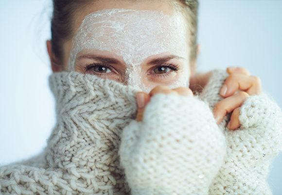 Kvinna med vit ansiktsmask som gömmer sig bakom en stickad polotröja