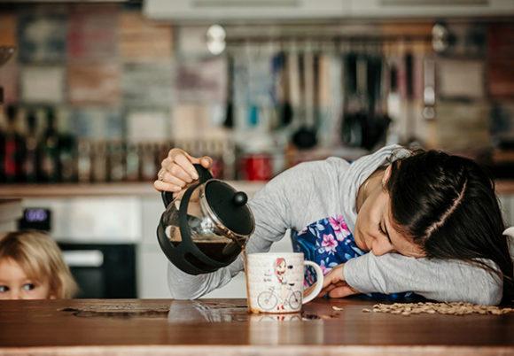 trött mamma häller upp kaffe