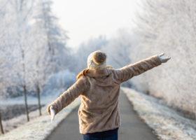 kvinna på vinterväg sträcker ut armarna