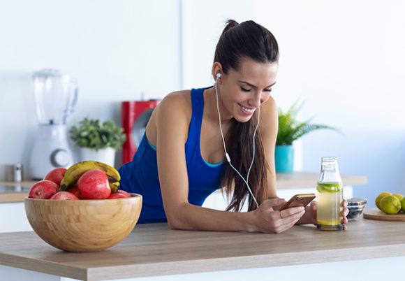 träningsklädd kvinna som har sund mat omkring sig