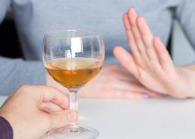 hand visar nej till ett glas vin