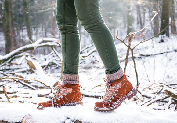 Ben i gröna jeans och kängor på skorna promenerar i skogen