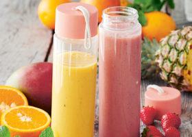 En gul och en rosa smoothie med frukt i bakgrunden