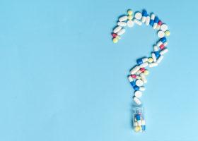 Medicinska piller format som ett frågetecken på blå bakgrund