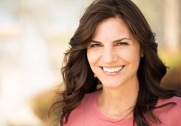 Mörkhårig 50-årig kvinna ler
