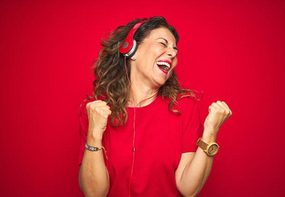 Glad kvinna gör segergest och lyssnar på musik i röda hörlurar med en röd bakgrund