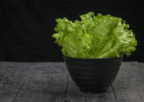En svart skål med salladsblad på ett svart träbord