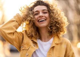 Ung kvinna med lockigt hår i gul jeansjacka, håller en hand i håret och ler