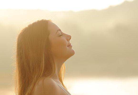 Kvinna som står i motljus och drar ett djupt andetag med stängda ögon