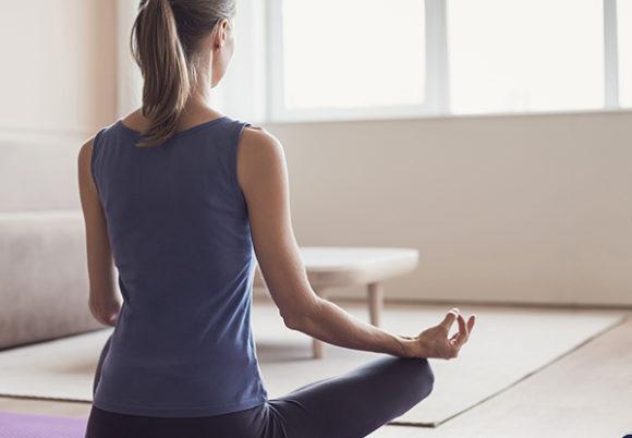 Kvinna syns yoga i skräddarställning bakifrån