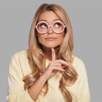 Ung kvinna med rosa glasögon och ett frågetecken på fingret tittar bort och funderar