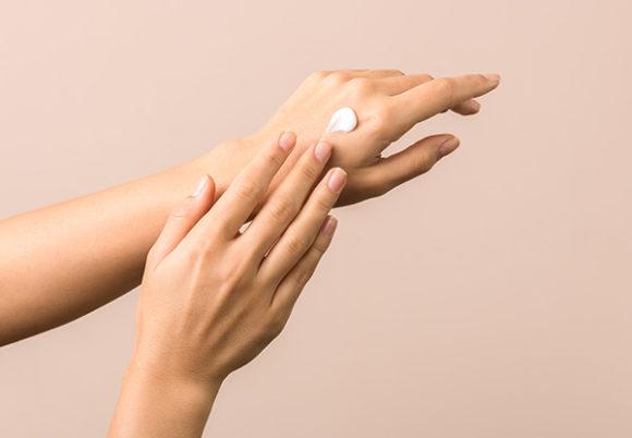 Smörjer in händer med lotion