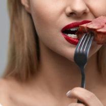 kvinna äter köttbit