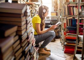 Ung kvinna sitter i ett bibliotek och läser