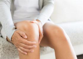 kvinna tar sig i sitt knä