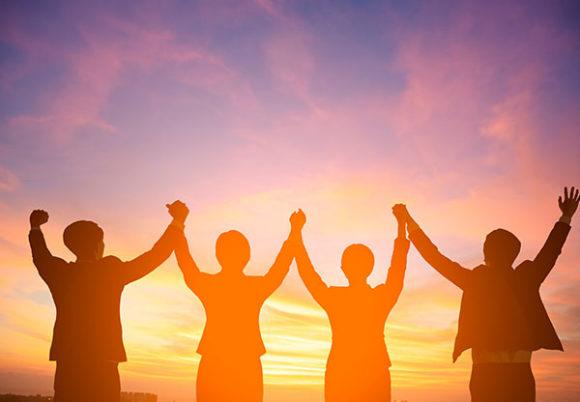 Fyra människor i soluppgång i motljus bakifrån