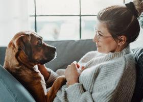 Kvinna i profil håller tassen på sin hund