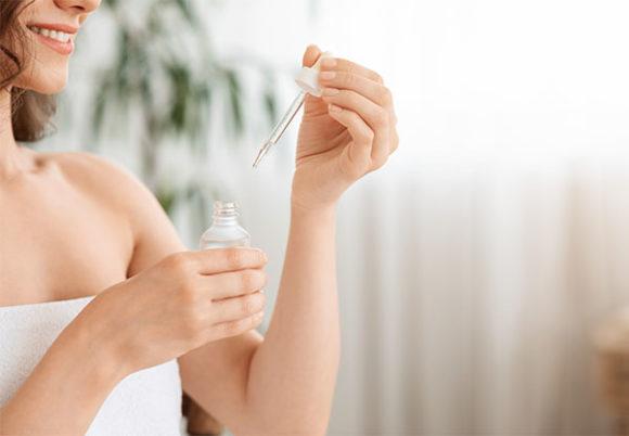 Kvinna håller i liten flaska och pipett för ansiktsvård