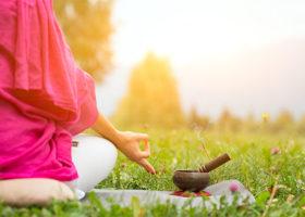 Kvinna i rosa blus, sedd bakifrån i lotusställning på en äng