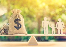 En gungbräda med en pengasäck och en familj som pappfigurer