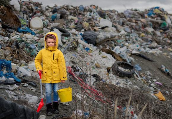 flicka står bland sopor