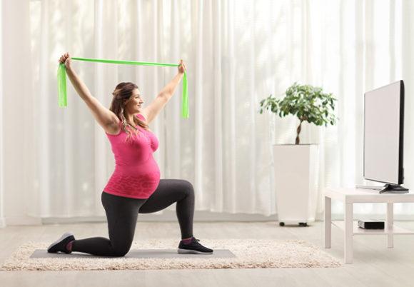 gravid kvinna tränar framför teven