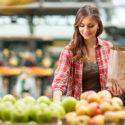 kvinna väljer frukt i butik