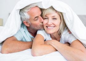 man och kvinna kikar fram under ett täcke