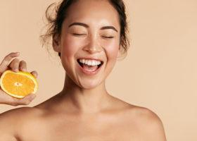 Leende kvinna blundar och håller i citrusfrukt i ena handen